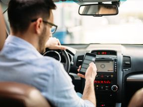 Stock photo of man using phone while driving the car