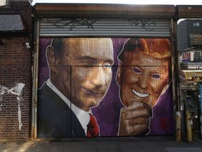 Mural depicting a winking Vladimir Putin taking off his Donald Trump mask on a storefront in Brooklyn, New York, on February 25, 2017