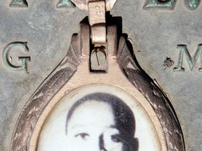 A photo of Emmett Till on the plaque that marks his gravesite at Burr Oak Cemetery in Illinois