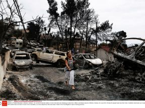 A woman walks among the burned out cars in Mati, east of Athens