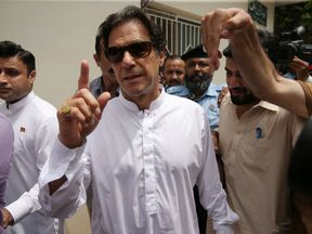 Imran Khan, chairman of Pakistan Tehreek-e-Insaf (PTI), arrives at a polling station during the general election in Islamabad