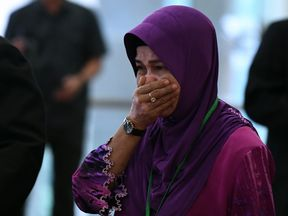 Sarah Nor, the mother of Norliakmar Hamid, a passenger on missing Malaysia Airlines flight MH370, cries as she arrives for the final investigation report on missing flight MH370 in Putrajaya, outside Kuala Lumpur on July 30, 2018. - Relatives of people aboard Flight MH370 said on July 30 they hoped a long-awaited report into the plane's disappearance might give them answers about one of the world's most enduring aviation mysteries