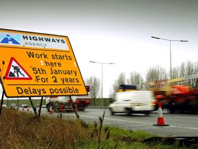 Cars drive past a sign on the M25 motorway informing them of road works