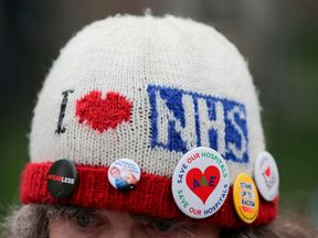 A protester wears badges on her hat as she attends a rally against private companies' involvement in the National Health Service (NHS) and social care services provision and against cuts to NHS funding in central London on March 4, 2017