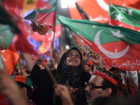 Supporters of Pakistani cricket star-turned-politician and head of the Pakistan Tehreek-e-Insaf (PTI) Imran Khan, cheer and wave flags during a rally during the last campaign day, in Lahore, on July 23, 2018
