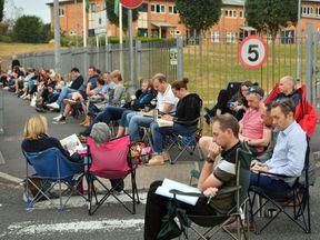 Parents queue in line outside Ysgol Y Berllan Deg school, Cardiff, for the breakfast club registration. Pic: Media Wales