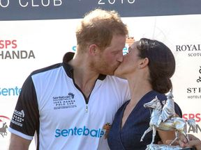 Meghan grabbed a kiss from her husband at the fixture