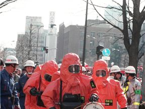 This picture taken on March 20, 1995 shows fire department officers moving into Kasumigaseki subway station following a sarin gas attack