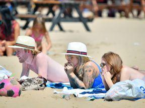 People sunbathe on the beach at Weston-super-Mare