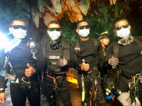 Four Thai navy SEALs give a thumbs up as they leave the cave
