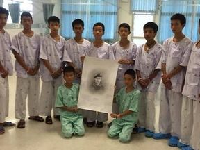 The boys with a picture of Saman Kunan who died during rescue mission