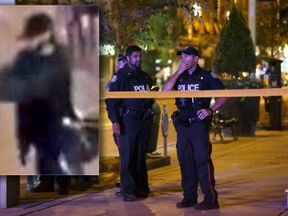 Toronto Police officers stand watch at Danforth St. at the scene of a shooting in Toronto