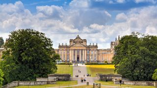 Woodstock, United Kingdom - June 27, 2015: Blenheim Palace, Woodstock, Oxfordshire, England. It is the principal residence of the dukes of Marlborough, and was built between 1705 and 1722. It is being used as a family home, mausoleum and national monument. The palace was also the birthplace of Sir Winston Churchill. Blue sky with clouds, landscaped lawn, green trees and sightseeing tourists entering the palace are in the image.