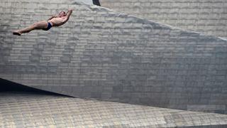 A contestant dives from a 27-metre platform on the La Salve bridge overlooking the Guggenheim Museum