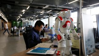 Staff work behind a robot at iCarbonX, a start up company in Shenzhen