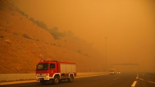 Fire fighters are seen amid smoke as a wildfire burns in Kineta