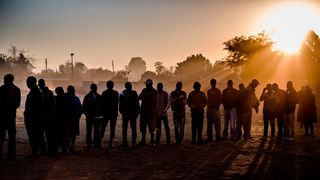 People queued as morning broke in the Mbare suburb of Harare