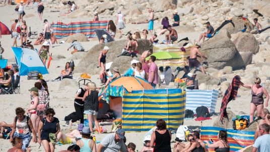 People enjoy the fine weather as they spend time on the beach at Sennen Cove near Penzance on June 28, 2018 in Cornwall, England. Parts of the UK are continuing to experience heatwave weather and record breaking temperatures