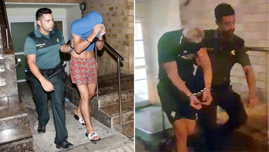Two British men are led away in handcuffs after being arrested over the alleged rape of a woman in Ibiza. Pic: Solarpix