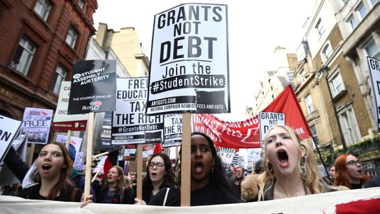 Protesters march with placards and banners against student fees during a  demonstration in central London in 2015.