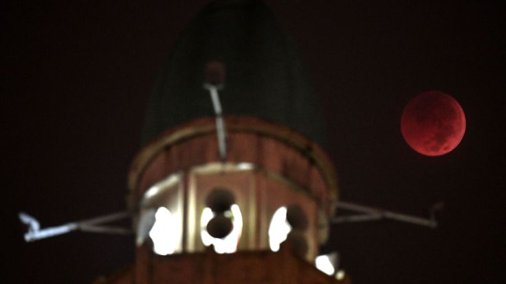 The moon appears beside the dome of the Wilayah mosque in Kuala Lumpur, Malaysia