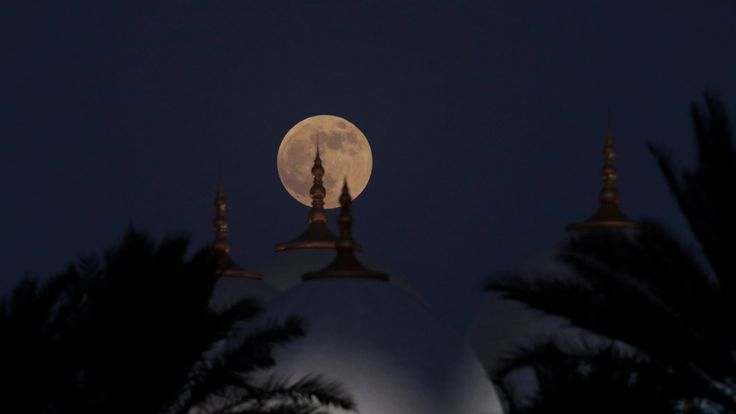 "A lunar eclipse of a full ""blood moon"" rises behind the Sheikh Zayed Mosque in Abu Dhabi, United Arab Emirates July 27, 2018. REUTERS / Christopher Pike"