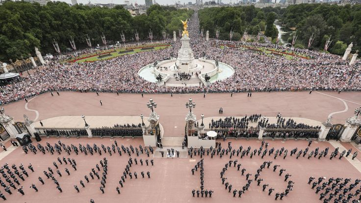 Service men and women spell out the number 100 in the forecourt of Buckingham Palace