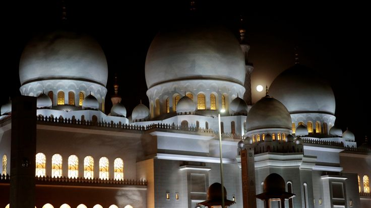 "A lunar eclipse of a full ""Blood Moon"" rises behind the Sheikh Zayed Grand Mosque in Abu Dhabi, United Arab Emirates July 27, 2018. REUTERS/Christopher Pike"