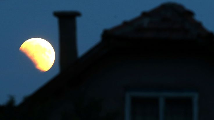 The moon rises behind a house in Zenica, Bosnia and Herzegovina