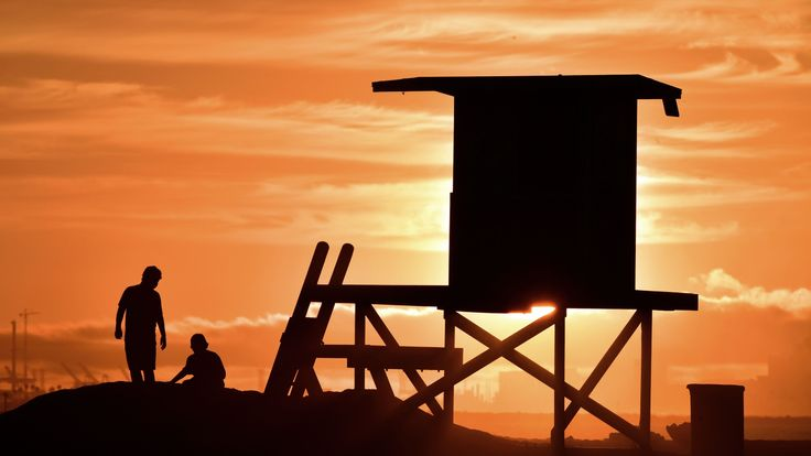 Children play beside a lifeguard tower as sunset approaches at Sunset Beach in Huntington Beach, California on July 21, 2018