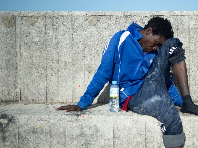 A migrant rests after arriving aboard a coast guard boat at Algecira's harbour