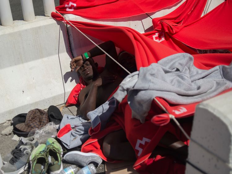 A man rescued at sea rests at the harbour of Algeciras