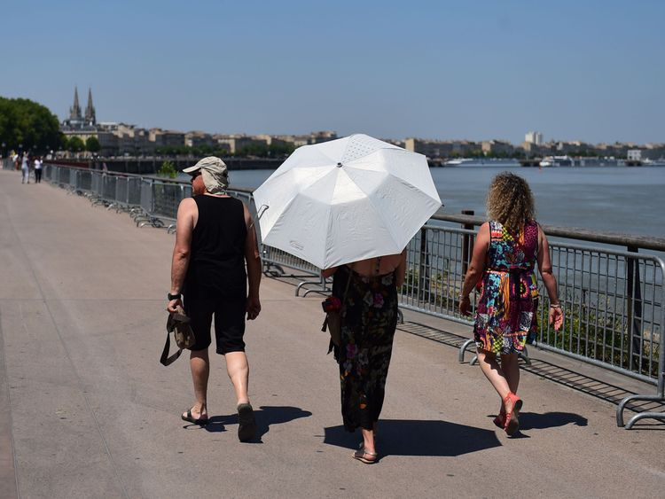 People walk on the banks of the Garonne river in Bordeaux, southwestern France