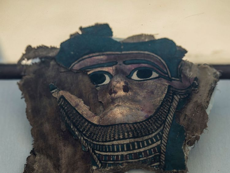 A picture taken on July 14, 2018 shows a broken gilded mummy mask on display in front of the step pyramid of Saqqara, south of the Egyptian capital Cairo. - The Egyptian Minister of Antiquities announced the excavation of a mummification workshop discovered along with a communal burial place, consisting of several burial chambers. The work is being carried out south of the King Unas Pyramid in Saqqara by an Egyptian-German mission. (Photo by Khaled DESOUKI / AFP) (Photo credit should read KHALED