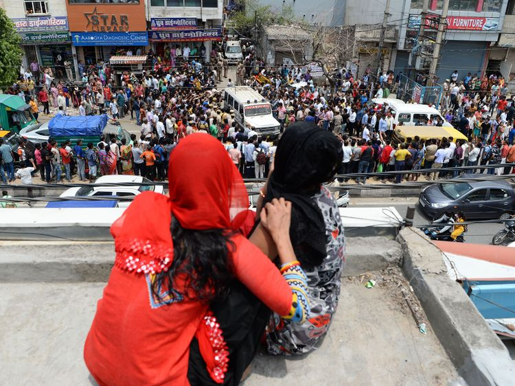 Women sitting on a rooftop watch as bystanders gather while an ambulance carrying bodies of victims drives out