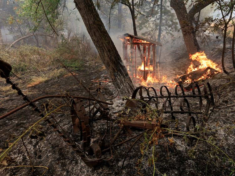 A wooden structure burns on the south edge of the Carr Fire near Igo, California