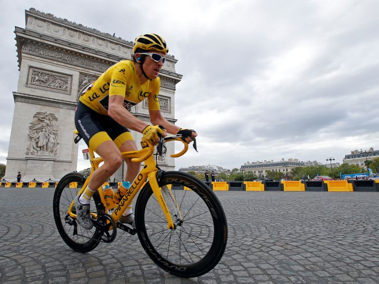 Team Sky rider Geraint Thomas of Britain wearing the overall leader's yellow jersey passes the Arc de Triomphe in the peloton