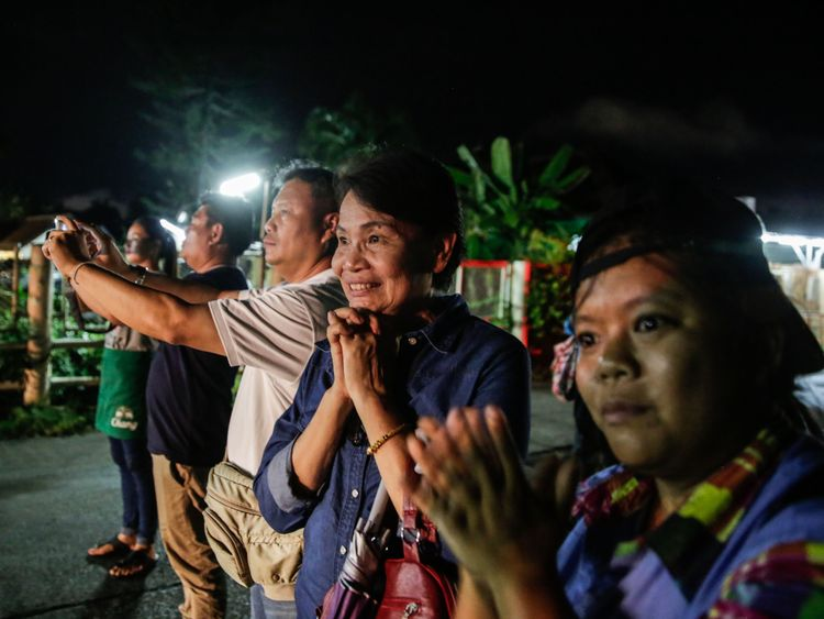 Onlookers watch and cheer as ambulances deliver boys rescued from a cave in northern Thailand to hospital in Chiang Rai after they were transported by helicopters on July 8, 2018 in Chiangrai