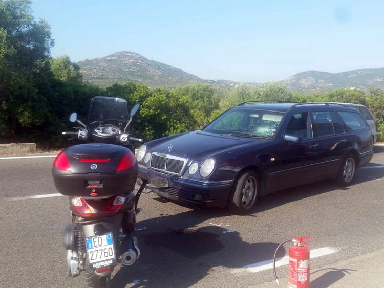 A motorcycle and car at the scene of the accident