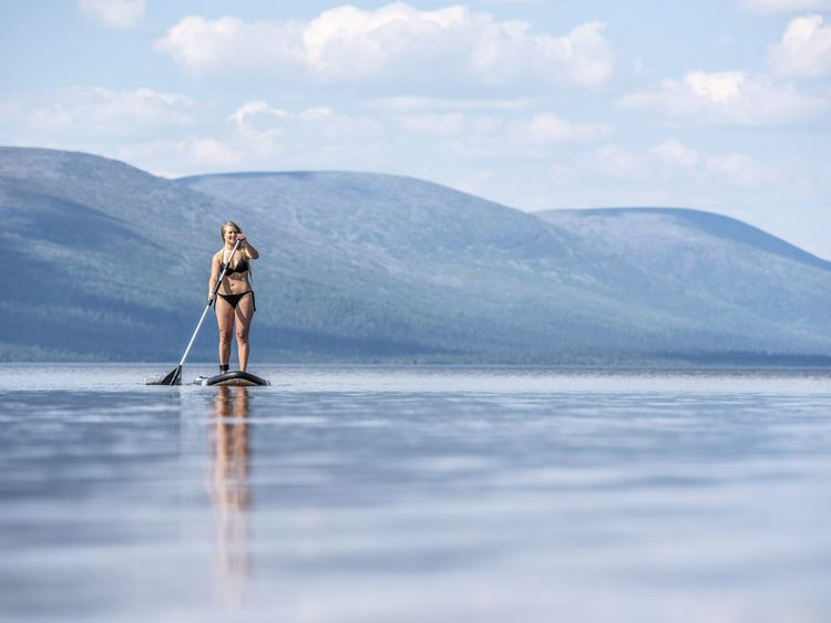 A bikini-clad woman on a surfboard in Finnish Lapland