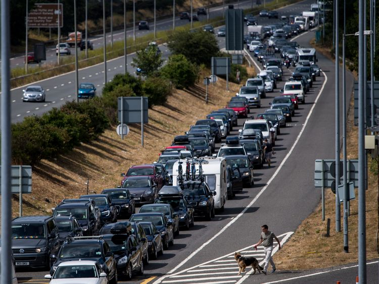 A holidaymaker walks his dog amongst stationary traffic as vehicles queue for Eurotunnel which is experiencing long delays due to extreme weather conditions on July 28, 2018 in Folkestone