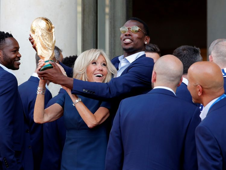 Brigitte Macron and midfielder Paul Pogba hold the trophy