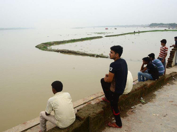 People look at the flooded banks of the Ganges river