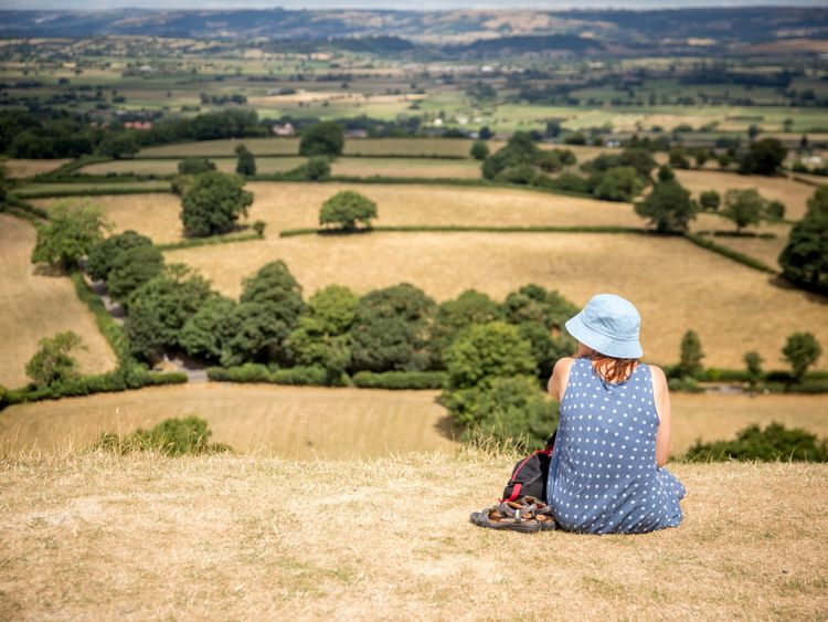 People sit on parched grass as they visit Glastonbury Tor in Glastonbury on July 24, 2018 in Somerset, England