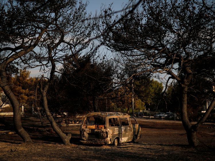 Burnt trees and a destroyed car are seen on a field following a wildfire at the village of Mati, near Athens, Greece, July 25, 2018. REUTERS/Alkis Konstantinidis
