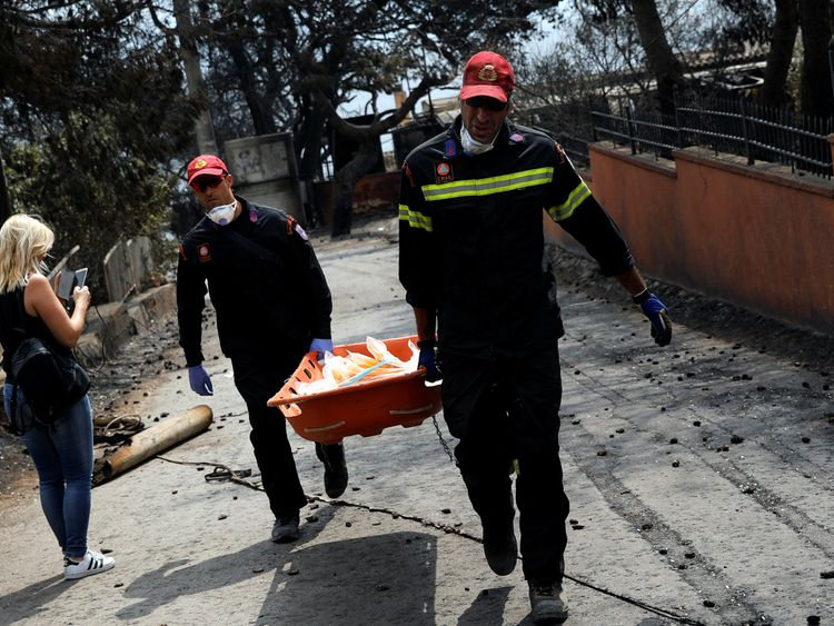 Firefighters carry a stretcher filled with body bags, following a wildfire at the village of Mati, near Athens, Greece, July 24, 2018. REUTERS/Alkis Konstantinidis