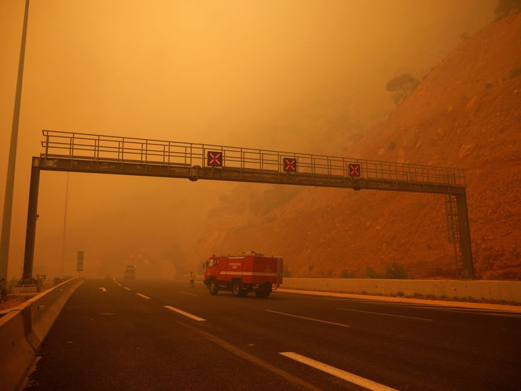 Smoke blankets a highway as a fire burns in Kineta, near Athens