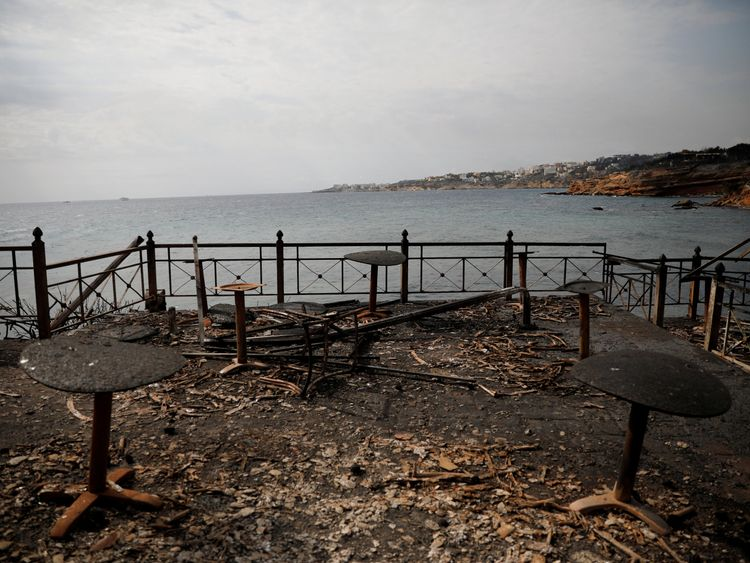 Tables and chairs of a seaside cafe following a wildfire at the village of Mati, near Athens