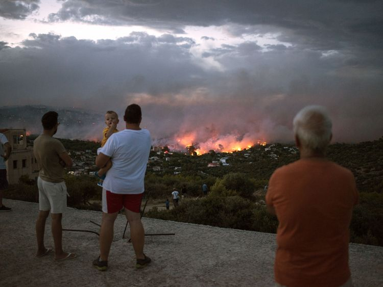 People watch the fires burn from a hilltop above Mati, Greece