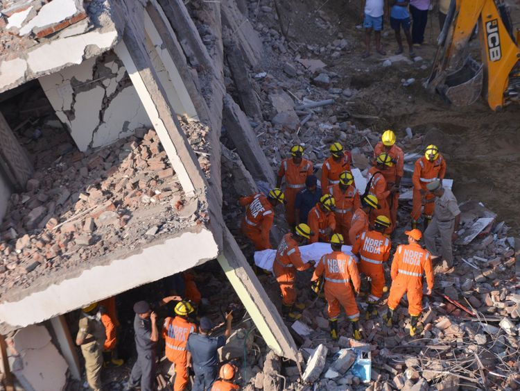 Members of the National Disaster Response Force remove a victim from the rubble